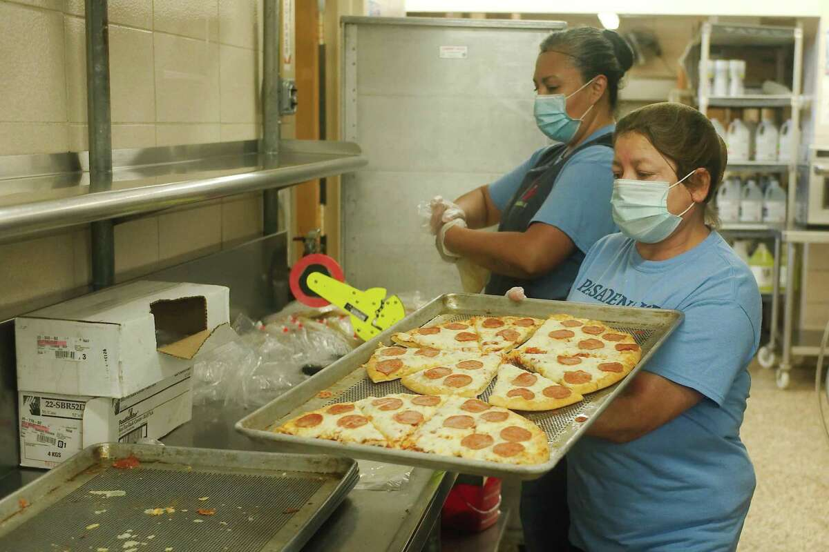 Margarita Duran and Monica Escalera bag slices of pizza to be included in the daily food package.