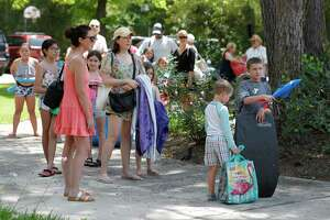 Residents wait as they line the path near Alden Bridge pool, Saturday, June 6, 2020, in The Woodlands. Alden Bridge is one of the seven pools operated by The Woodlands Township that opened Saturday at 25 percent occupancy and other safety guidelines. The pools are opened from noon to 6:00 p.m. Tuesday through Sunday. With the closure of the Harper's Landing swimming pool, only six community pools remain open.