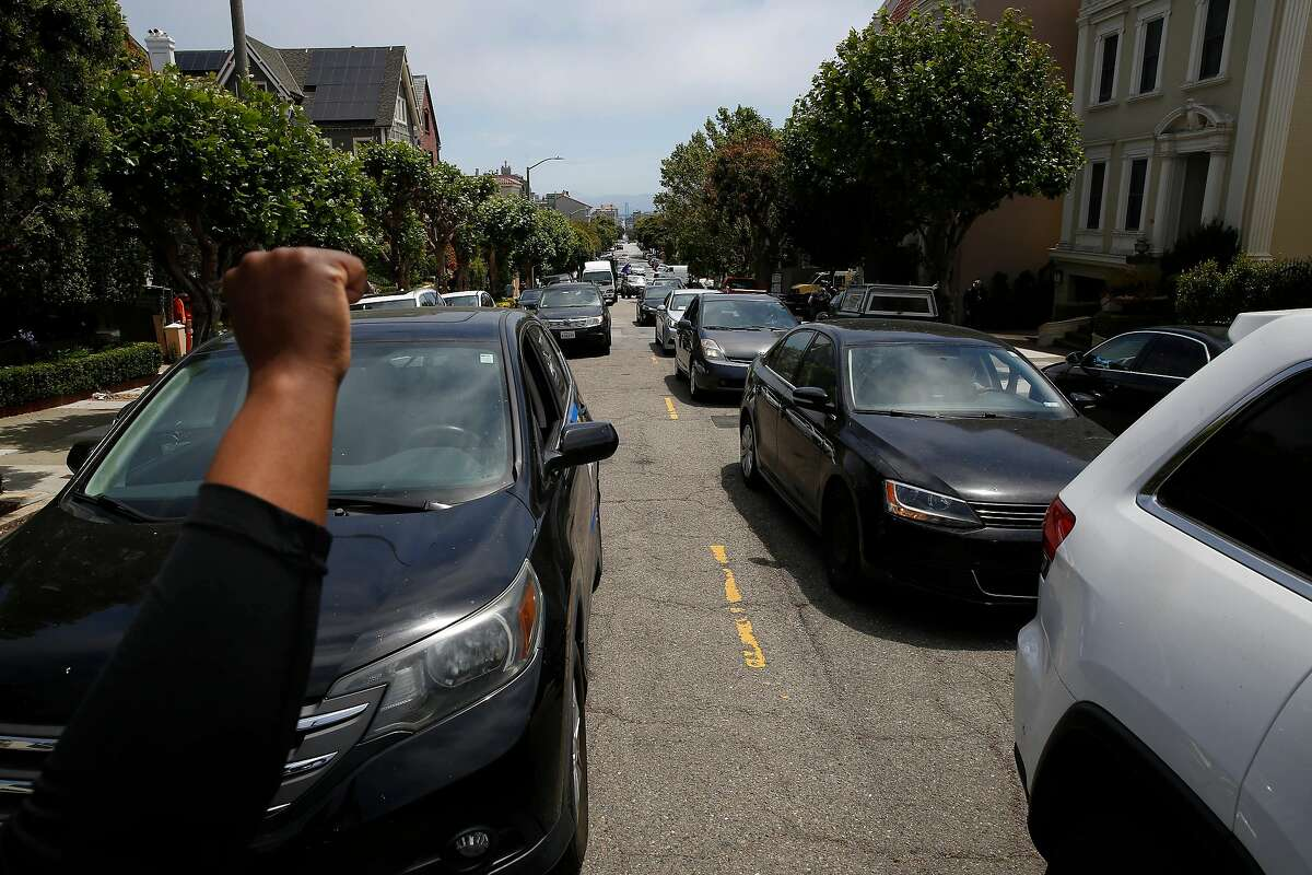 Minister Cherri Murphy (left), Gig Workers Rising organizer, pumps her first in the air toward the driver caravan as people drive away from the protest that was held in front of Uber CEO Dara Khosrowshahi's home on Wednesday, June 24, 2020 in San Francisco, Calif.