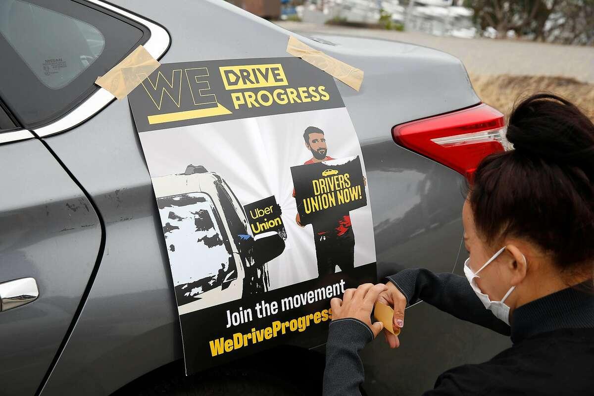 Saori Okawa, who drives for Uber, tapes a poster to the car of Rosa Mendoza at the Marina Green before the driver caravan protesting Uber's