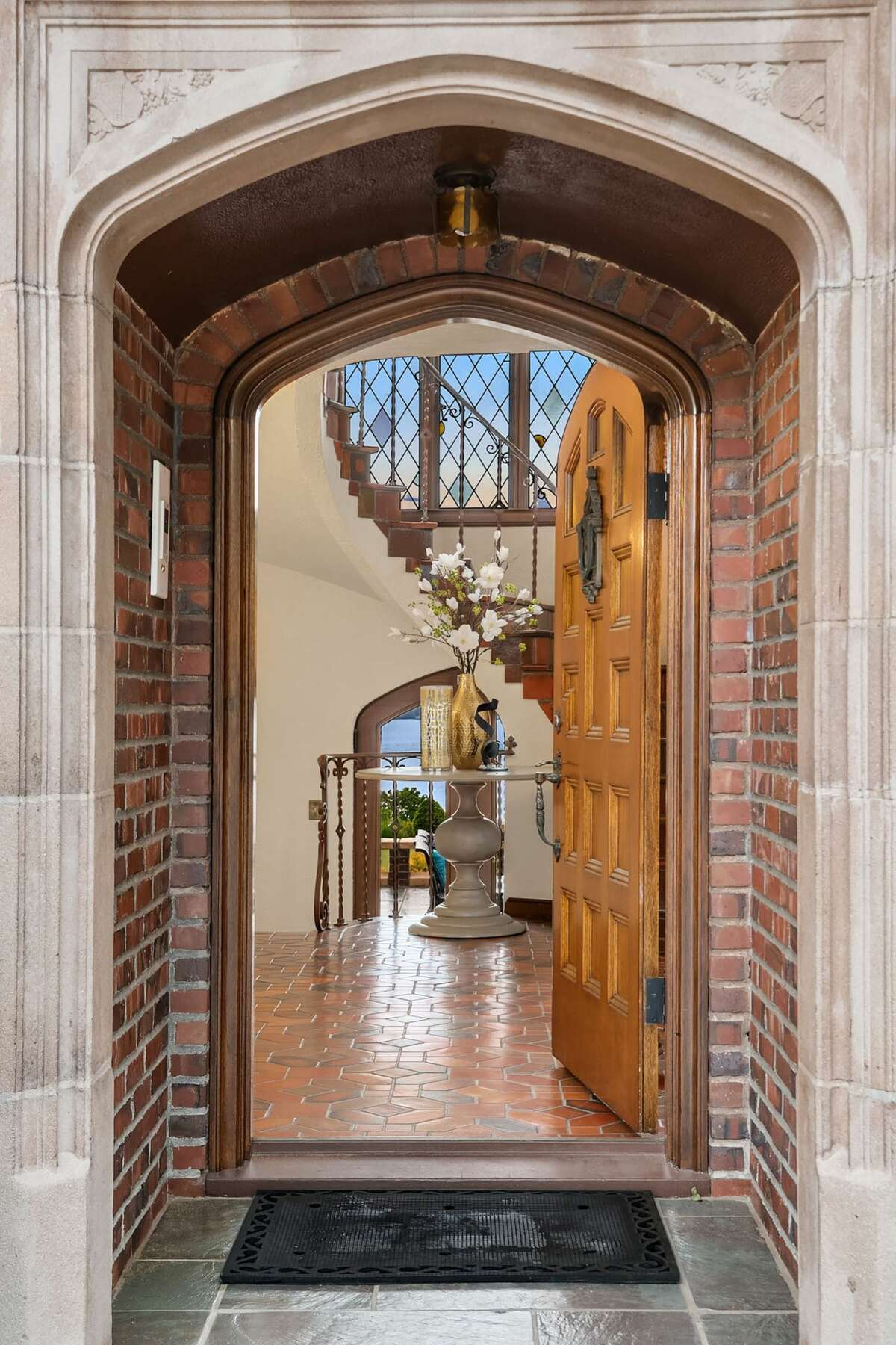 If the entrance seems grand, it is: 2-ton polished stone of Chinese jade and marble gives way to the foyer and the original leaded glass windows beyond.