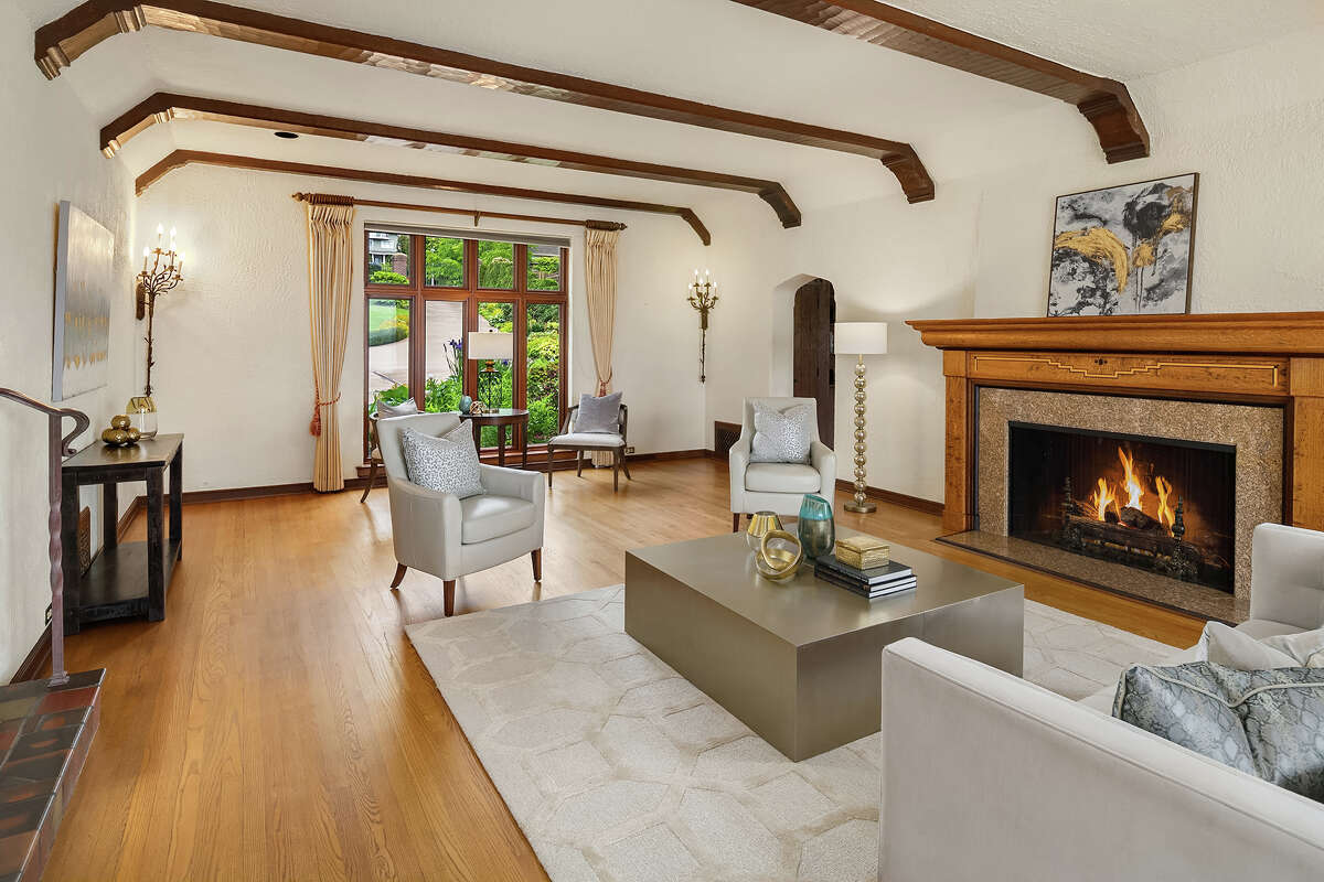 The original hand-hewn timbers frame the main living room. The home also offers 4 fireplaces.