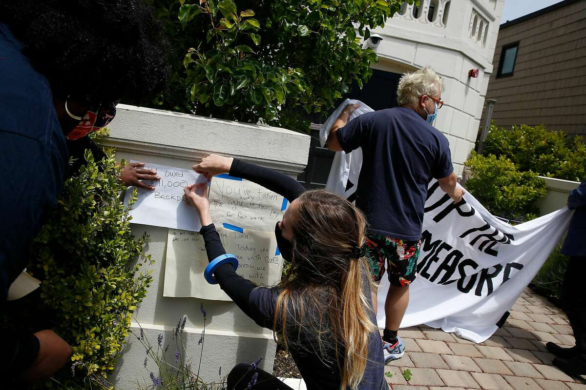 """Minister Cherri Murphy (left), and Lauren Casey (second from left), both Gig Workers Rising organizers, post """"grievance notes"""" on a post at the front of Uber CEO Dara Khosrowshahi's home during a driver caravan protest on Wednesday, June 24, 2020 in San Francisco, Calif."""