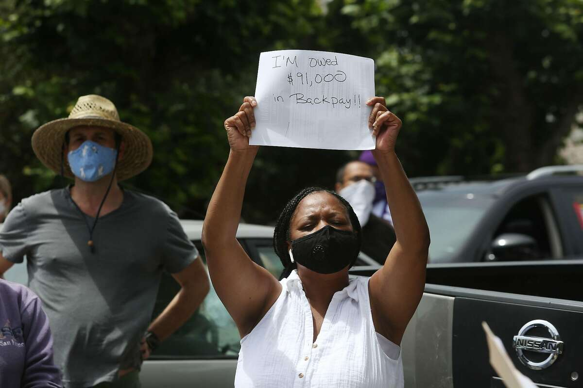 Catherine London, Lyft driver, holds a sign as she stands with others while listening to speakers during a driver caravan protest at the front of Uber CEO Dara Khosrowshahi's home on Wednesday, June 24, 2020 in San Francisco, Calif.