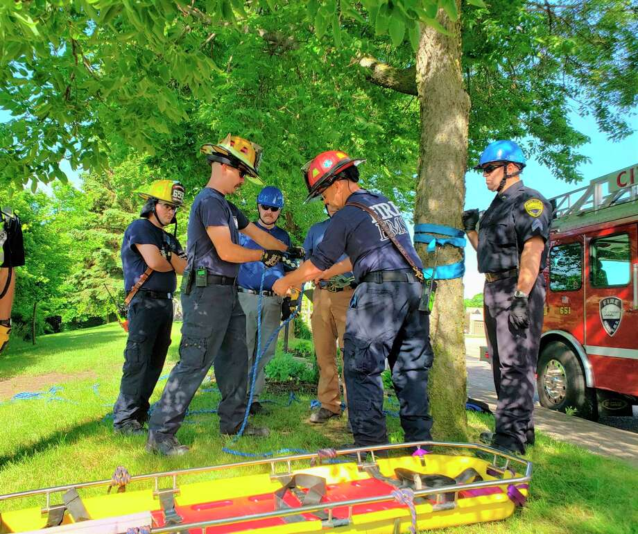 Personnel from local fire and police departments trained for low angle rescue situations by setting up an anchor and mechanical advantage with pulleys attached to a tree near the Manistee River channel's steep hillside Wednesday. (Arielle Breen/News Advocate)