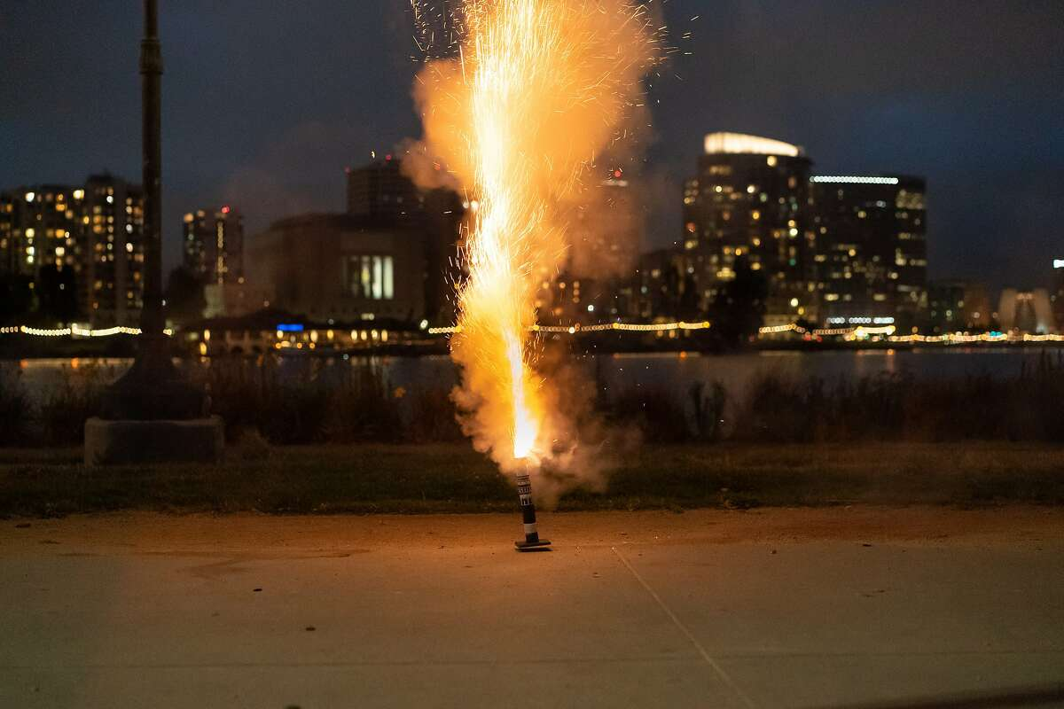 Rocky, he asks to not reveal his last name, ducks as his up mortar firework launches at Lake Merritt on Wednesday, June 24, 2020 in Oakland, Calif. He was there with his friends who also enjoyed fireworks.