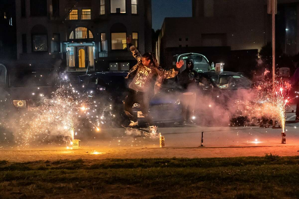 A man who just moved from NY, skate boards past a line of sparklers with a group of friends to continue the celebration of Juneteenth and hang out at Lake Merritt on Wednesday, June 24, 2020 in Oakland, Calif.