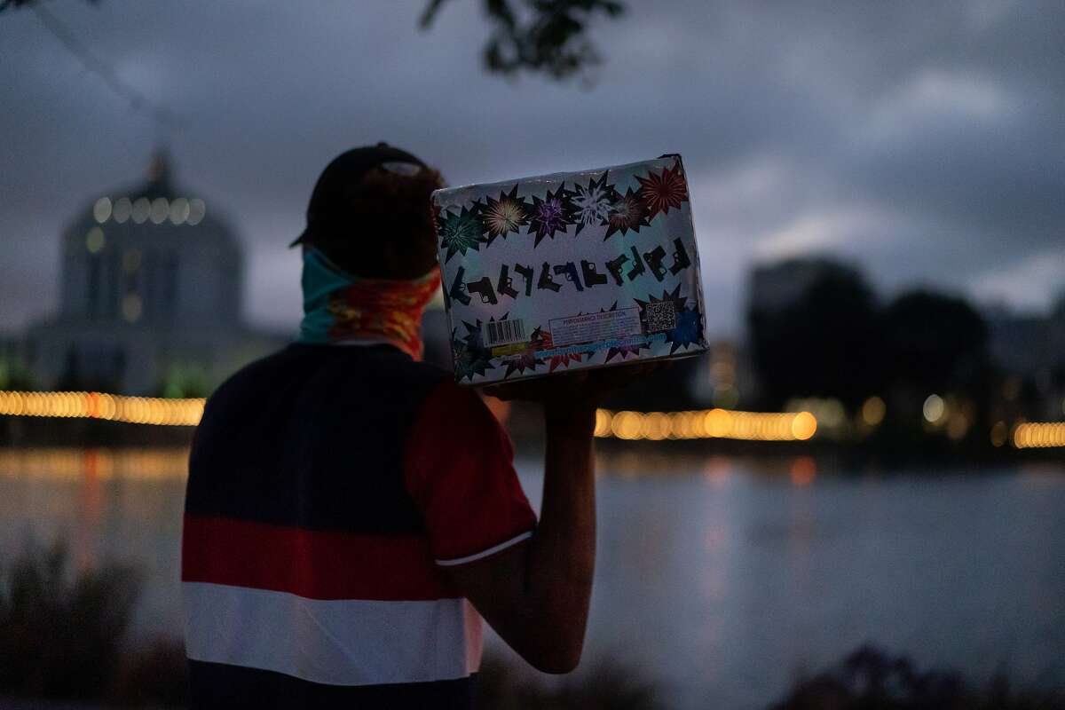 Rocky, he asks to not reveal his last name, carries his mortar firework, with multiple aerial bursts, at Lake Merritt on Wednesday, June 24, 2020 in Oakland, Calif. He was there with his friends who also enjoyed fireworks.