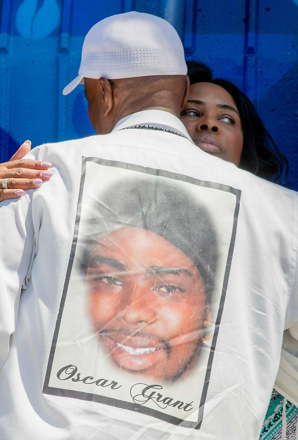 Wanda Johnson, mother of the late Oscar Grant, greets Oscar's uncle Bobby Johnson while standing underneath a large mural honoring her son during a mural and street naming unveiling for Oscar Grant at Fruitvale BART Station in Oakland, Calif. Saturday, June 8, 2019.