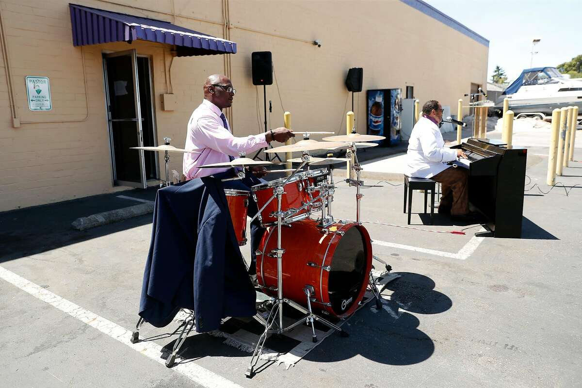 Willie Dudley plays the drums as Pastor D.M. Phillips sings and plays the organ during Greater Grace Temple Church's service in the parking lot of the church in San Leandro, Calif., on Sunday, June 21, 2020.