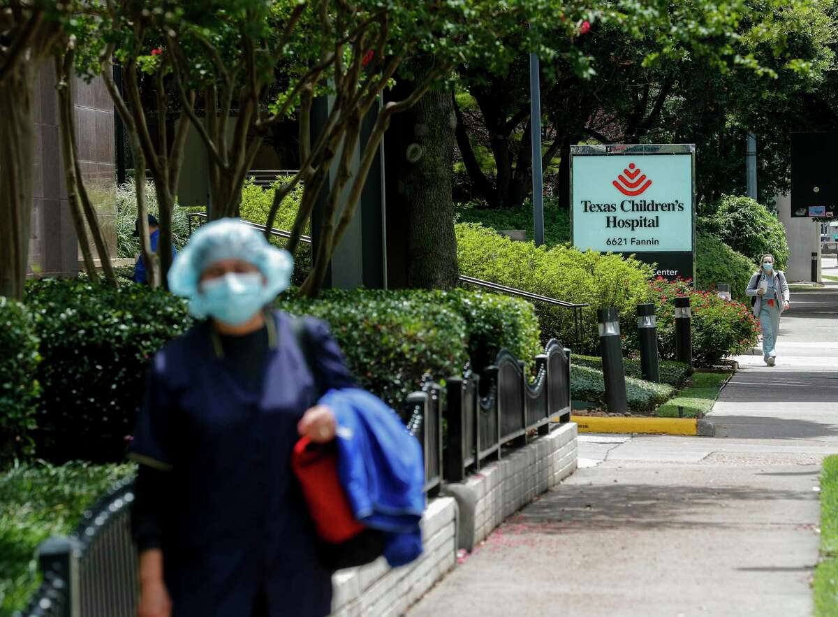 Medical professionals walk along Fannin Street in The Medical Center on Wednesday, June 24, 2020, in Houston. The Medical Center released the most aggressive COVID model to date, showing base ICU base capacity full by Saturday, and surge capacity exhausted by July 8 if current rates of hospitalization persist.
