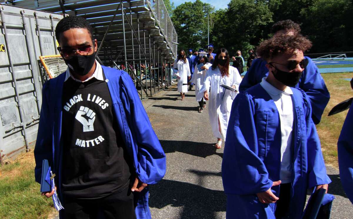 A graduate wears a Black Lives Matter T-shirt under his robe during Bunnell High School's Sixtieth Commencement in Stratford, Conn. on Friday June 24, 2020.