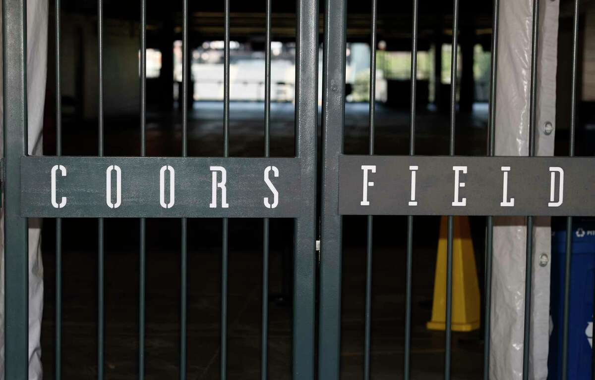The main gate of Coors Field, home of the Major League Baseball team the Colorado Rockies, is locked early Tuesday, June 23, 2020, in Denver. The league is waiting for the players' union to respond Tuesday to whether it will agree to health protocols for a 60-game regular-season slate and if players will report for training camp by July 1. (AP Photo/David Zalubowski)