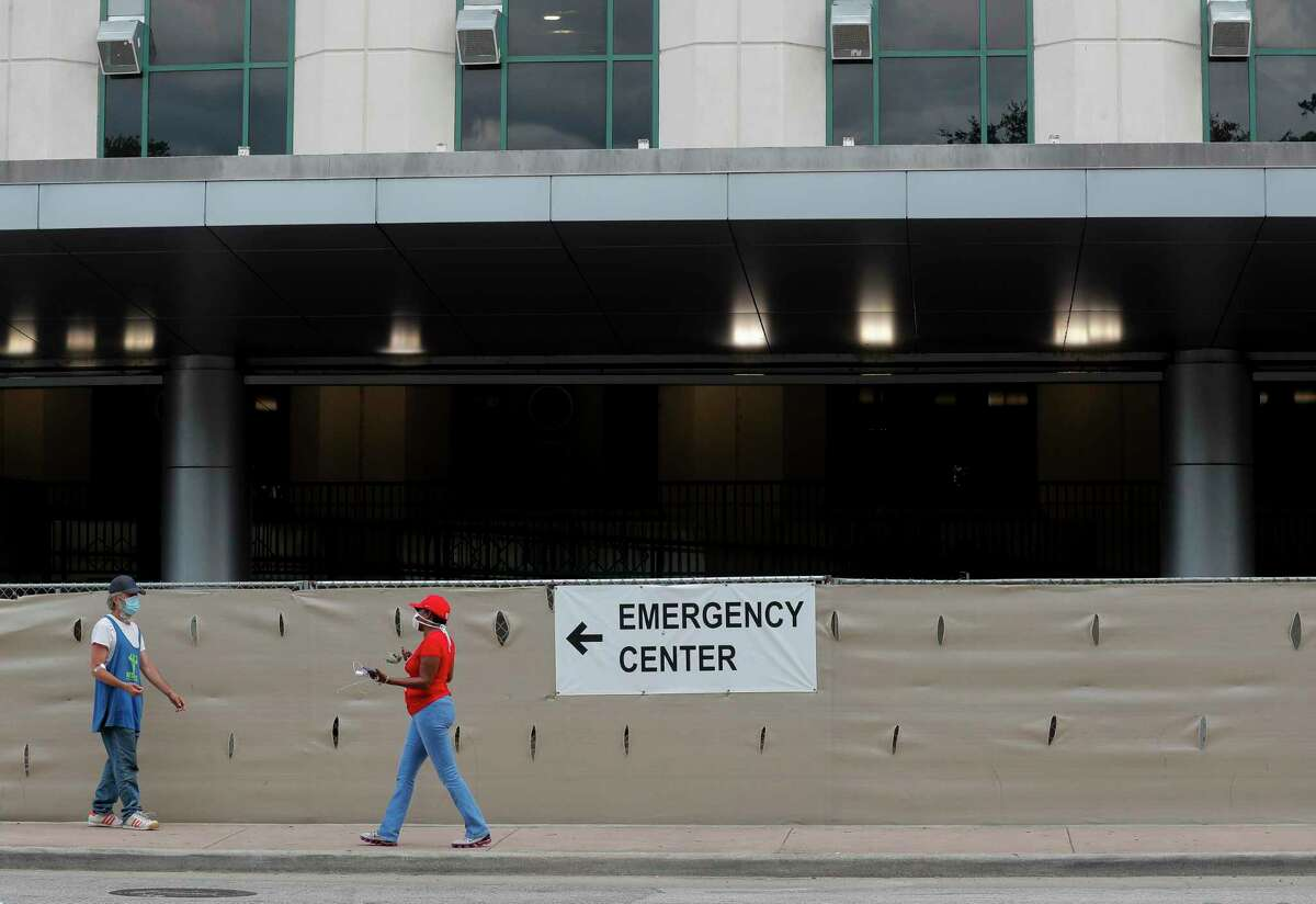 Two people walk along Cambridge Street in The Medical Center on Wednesday, June 24, 2020, in Houston. People might be especially concerned about having health coverage this year because they're worried about needing medical services during a pandemic, or because they've lost income and job-based insurance and need an affordable option, said Stacey Pogue, a senior policy analyst at Every Texan, an Austin think tank.