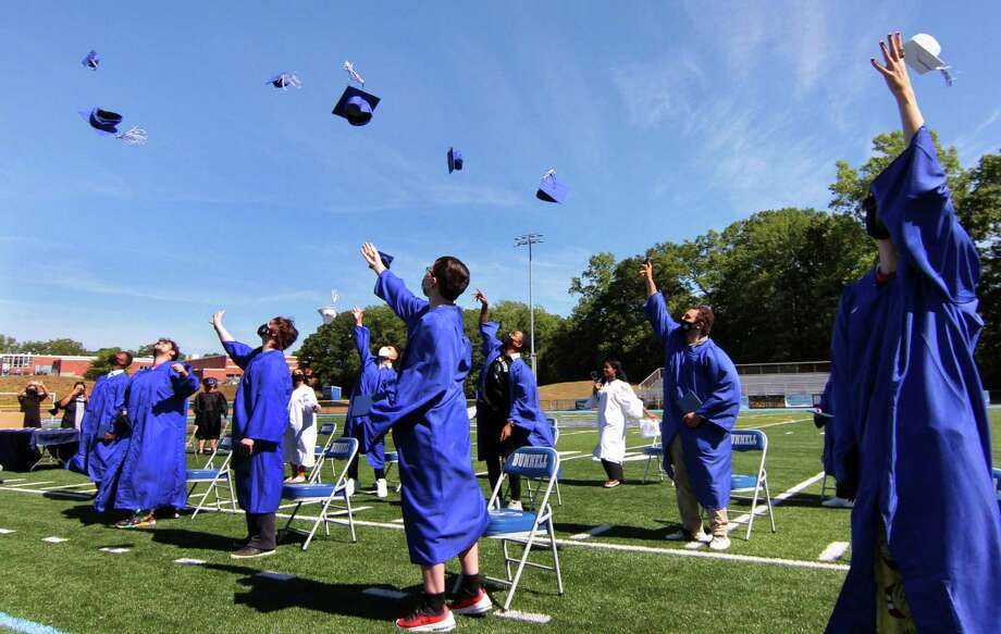 A small group of graduates throw their caps into the air in celebration during Bunnell High School's 60th commencement in Stratford on Wednesday. To observe social distancing, graduates came in groups of 15 and walked onto the football field with their families. Photo: Christian Abraham / Hearst Connecticut Media / Connecticut Post