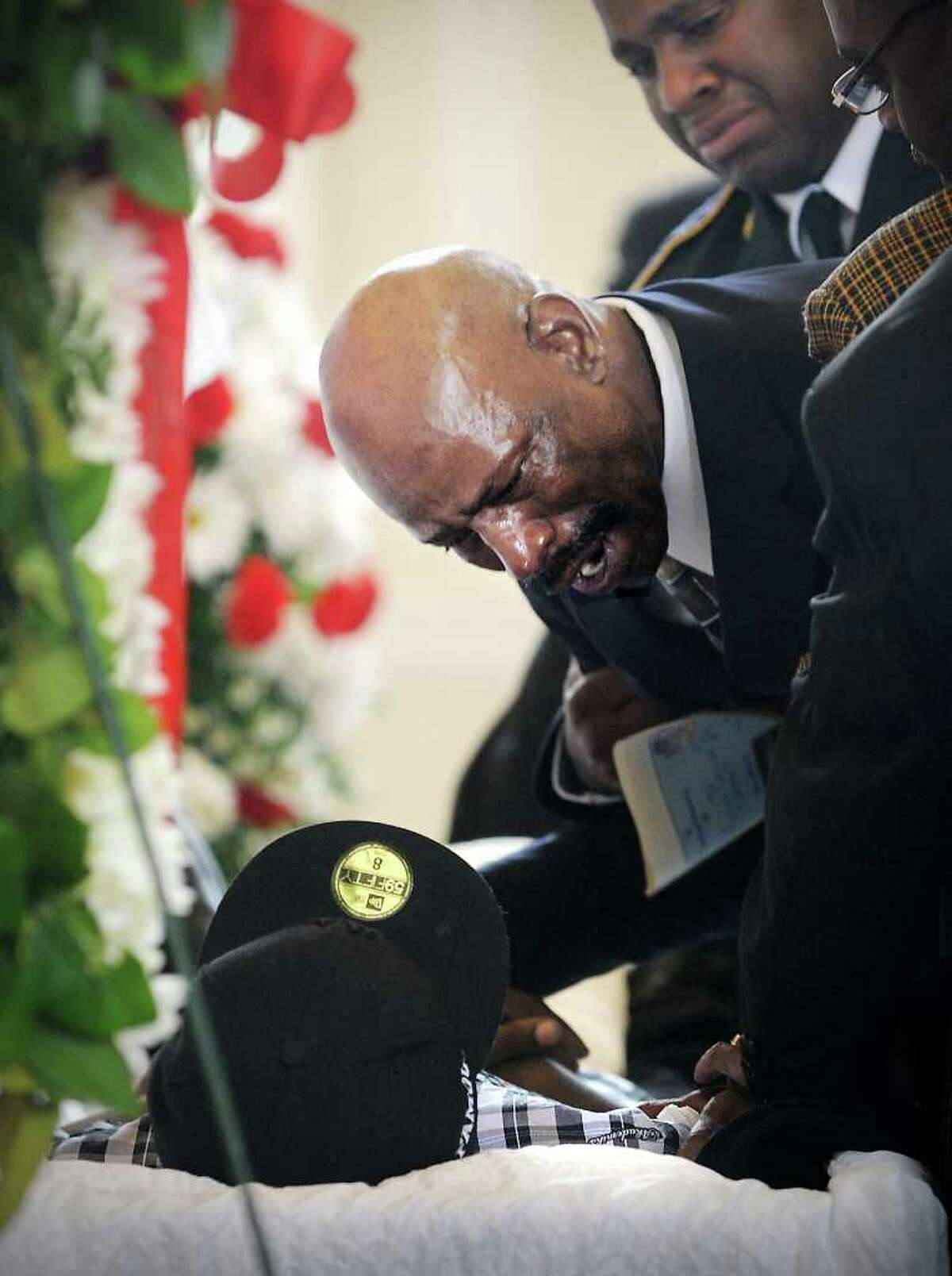 """Amos Brown, Sr. stands by the casket of his son Amos """"A.J."""" Brown, who was gunned down in Norwalk earlier this month, during the funeral at First Congregational Church in Norwalk, Conn. on Tuesday August 24, 2010."""