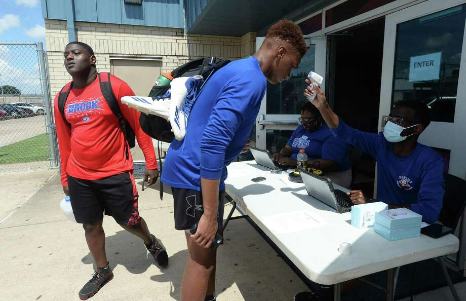 Athletes have their temperatures taken as they check in on the first day of summer conditioning at West Brook Monday morning. While most schools started the summer workouts when the state permitted last week, BISD programs waited until this week to hold camps. Photo taken Monday, June 15, 2020 Kim Brent/The Enterprise Photo: Kim Brent / The Enterprise / BEN