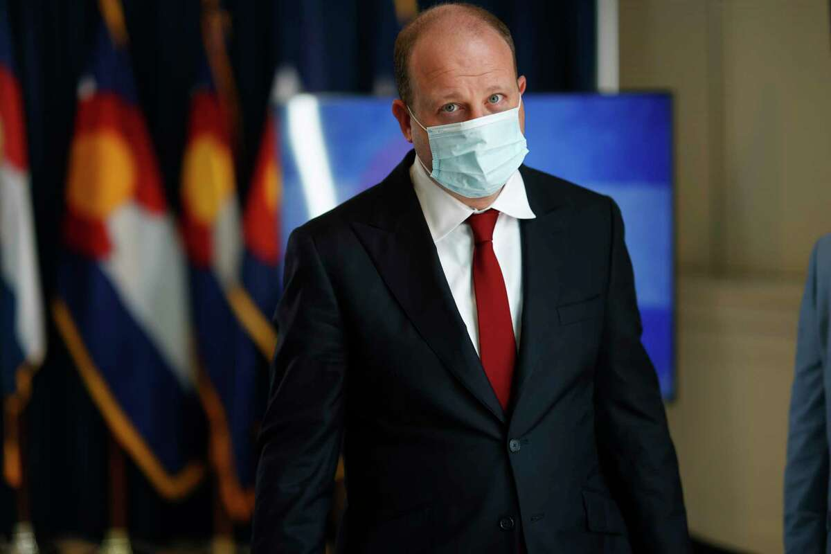 Colorado Governor Jared Polis wears a face mask as he leaves a news conference about the state's efforts to stop the spread of the new coronavirus Wednesday, June 24, 2020, in Denver.