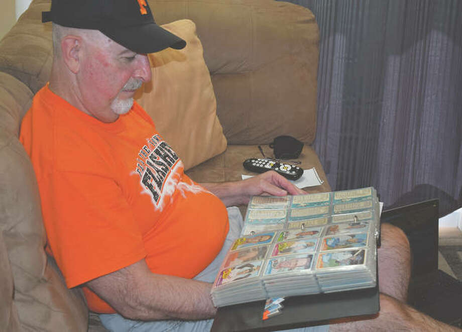 Greg Tabeek looks at his baseball card collection, which he hopes to continue developing as he retires from education. Photo: Samantha McDaniel-Ogletree | Journal-Courier
