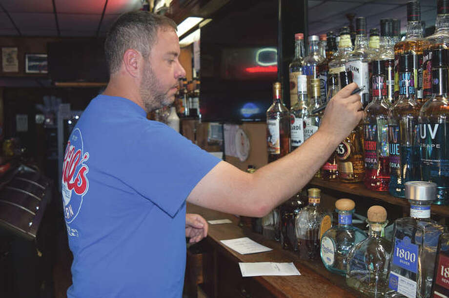 Brett Hannant, owner of Bill's West State Tavern, prices liquor Wednesday. Bill's West State Tavern has been shut down for the duration of the state's shelter-in-place order.