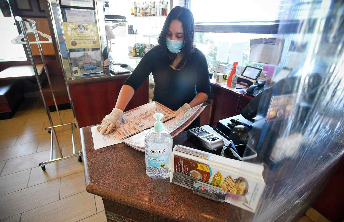 Vanity Melendez sanitizes menus while waiting to seat patrons dining at Bull's Head Diner in Stamford, Connecticut on June 17, 2020.