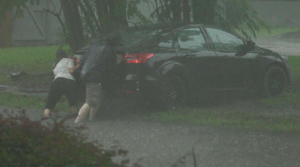 Two people try and push their car to safety after getting caught in a flooded Hillcroft Avenue near Rutherglen Drive on Thursday, June 25, 2020.