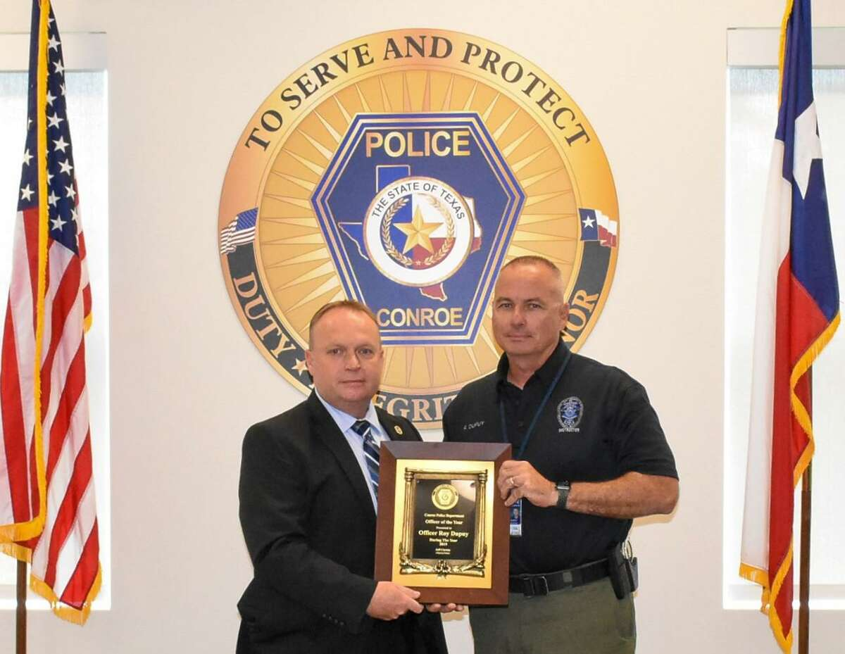 Conroe Police Department Chief Jeff Christy presents Officer Roy Dupuy with a plaque recognizing him as officer of the year at an awards ceremony.