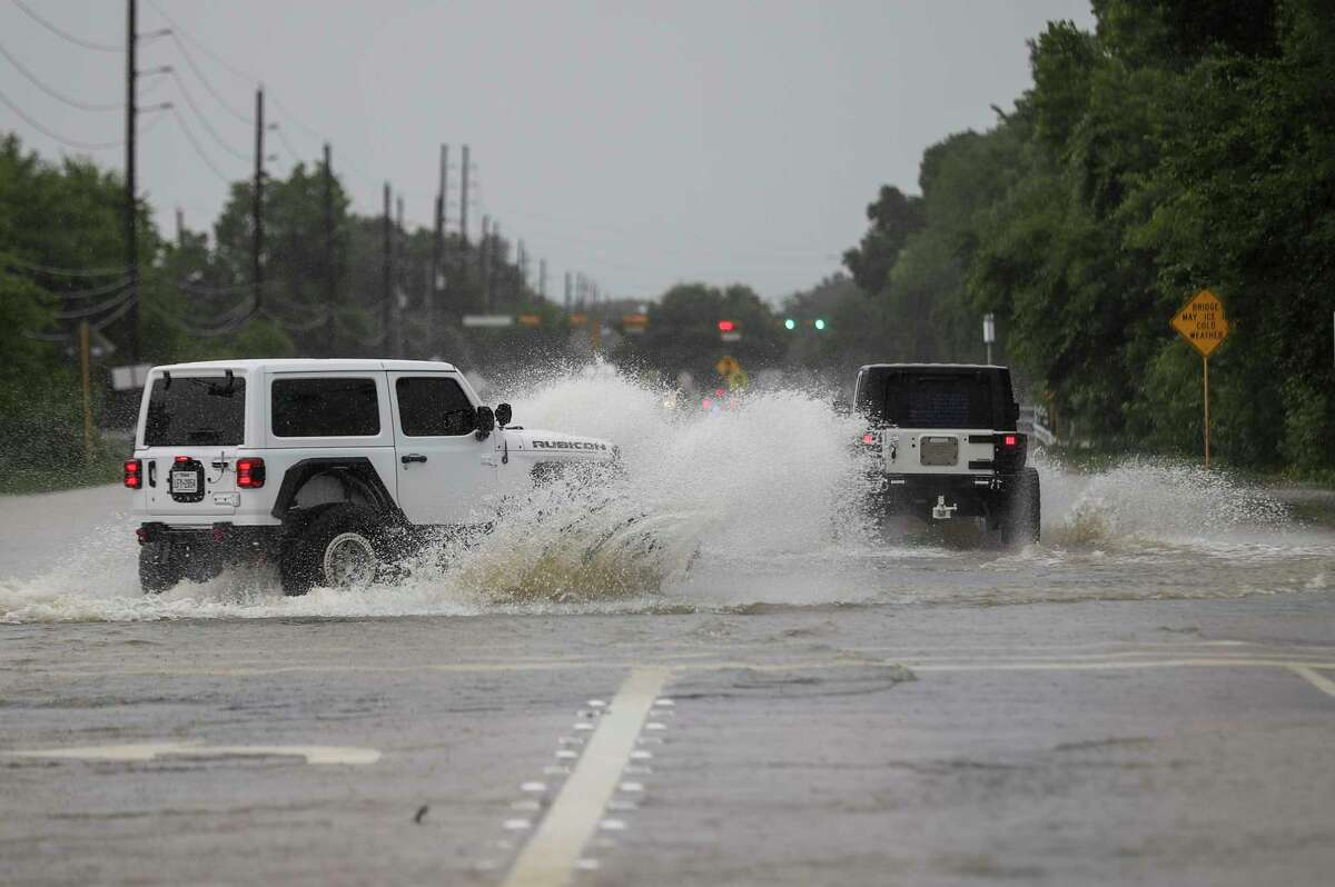 People drive jeeps through high water as areas around South Mayde Creek flood Thursday, June 25, 2020, at the intersection of Greenhouse Road and Saums Road in Houston.