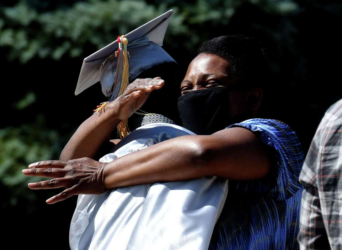 Niskayuna High School senior Ansley Deronceray receives a loving embrace from his mother, Annecy, during a graduation ceremony on Thursday, June 25, 2020, in Niskayuna, N.Y. Deronceray will attend SUNY Albany/SUNY Upstate Medical University, according to the school's newsletter. (Will Waldron/Times Union)