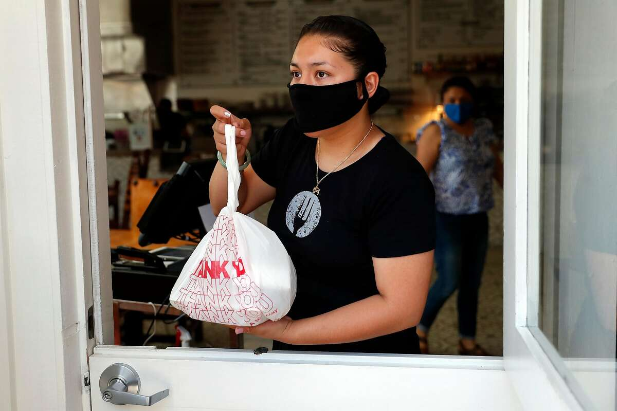 El Huarache Loco's Dayana Salazar hands out a pick up order as her mother, Veronica, stands behind her at the restaurant in Larkspur, Calif., on Wednesday, June 17, 2020. Dayana, who is undocumented, and her family run the restaurant in Marin Country Mart.
