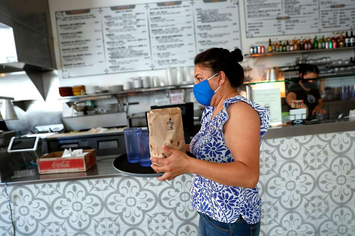 El Huarache Loco's Veronica Salazar takes a lunch order outside to a waiting customer in Larkspur, Calif., on Wednesday, June 17, 2020. Dayana Salazar, who is undocumented, and her family run the restaurant in Marin Country Mart.