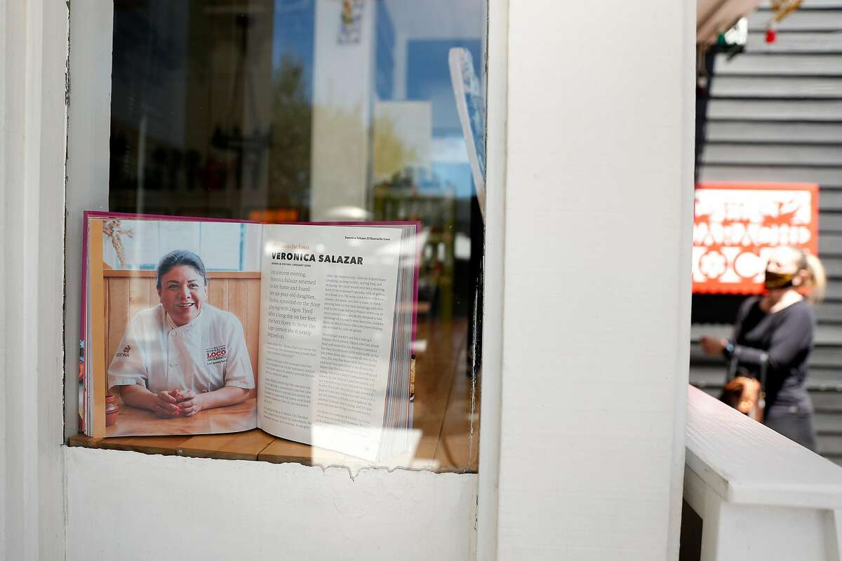A book highlighting Veronica Salazar in the front window of El Huarache Loco in Larkspur, Calif., on Wednesday, June 17, 2020. Dayana Salazar, who is undocumented, and her family run the restaurant in Marin Country Mart.