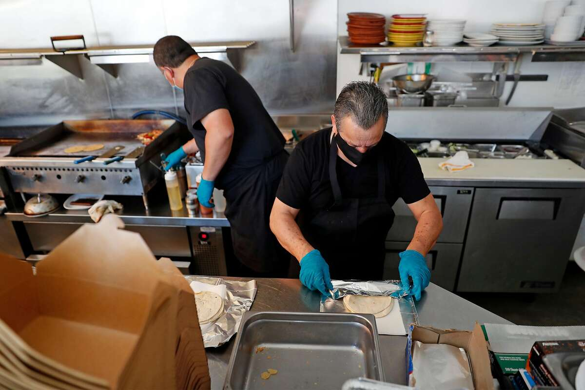 El Huarache Loco's Don Jose Luis and Miguel Perez workson lunch orders in Larkspur, Calif., on Wednesday, June 17, 2020. Dayana Salazar, who is undocumented, and her family run the restaurant in Marin Country Mart.