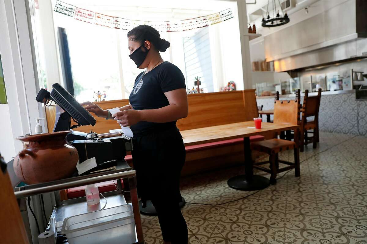 El Huarache Loco's Dayana Salazar works the register at the restaurant in Larkspur, Calif., on Wednesday, June 17, 2020. Dayana, who is undocumented, and her family run the restaurant in Marin Country Mart.