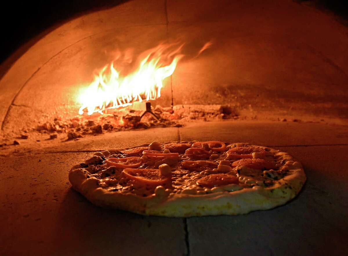 A pizza cooks in the wood-fired pizza oven at DeFazio's on Thursday, June 25, 2020 in Troy, N.Y.