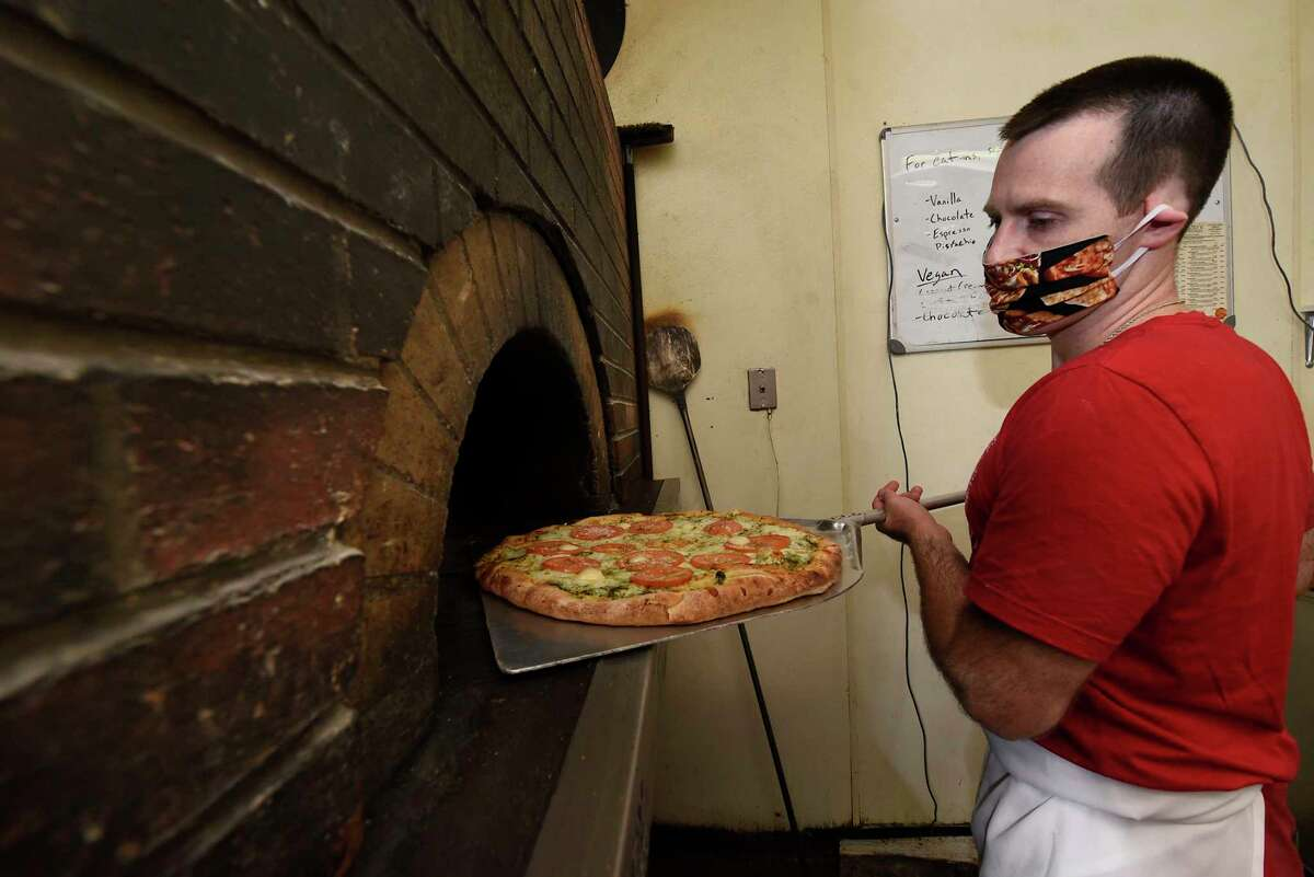 Matthew DeFazio wears a protective face mask as he takes out a pesto pizza from wood-fired pizza oven at DeFazio's on Thursday, June 25, 2020 in Troy, N.Y. (Lori Van Buren/Times Union)
