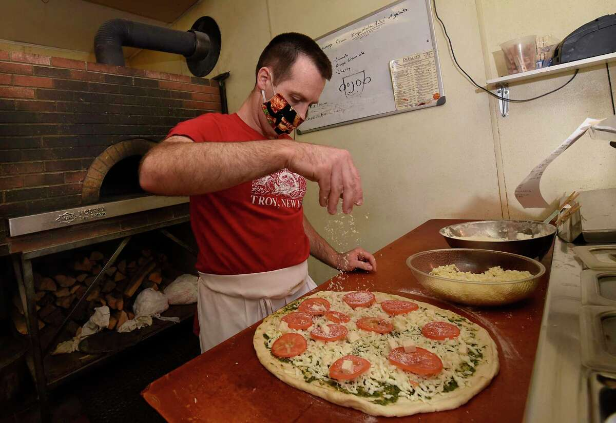 Matthew DeFazio wears a protective face mask as he makes a pesto pizza to put the wood-fired pizza oven at DeFazio's on Thursday, June 25, 2020 in Troy, N.Y. (Lori Van Buren/Times Union)