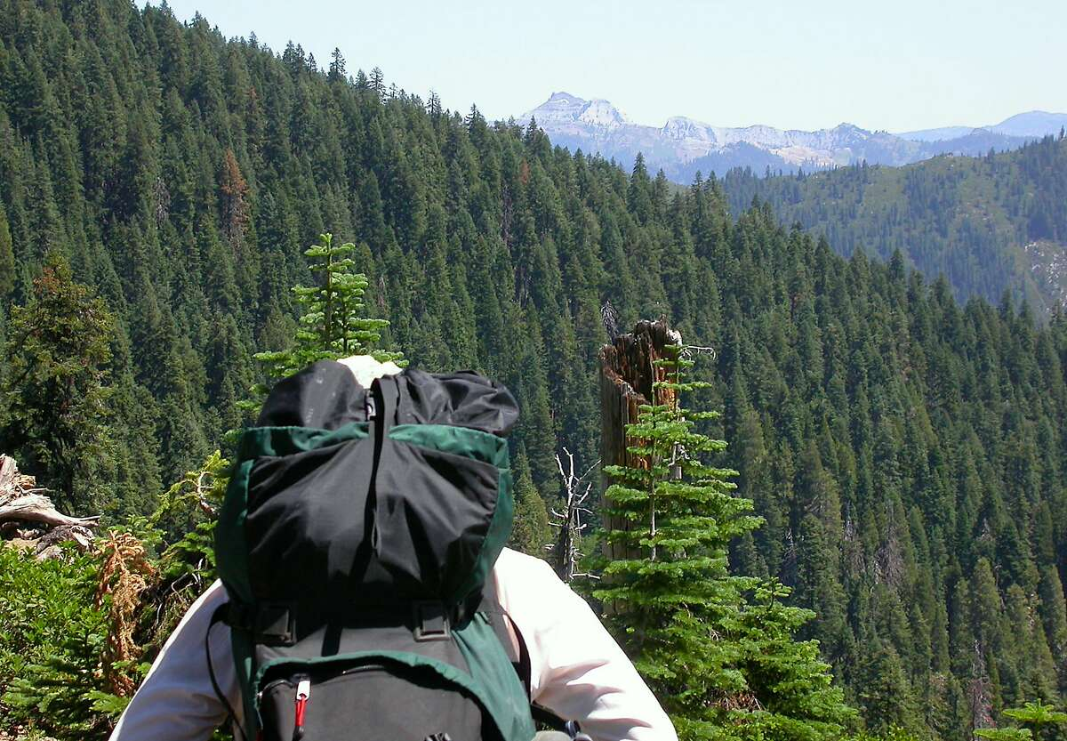 Hikers takes in view of Marble Mountain on horizon in Marble Mountain Wilderness