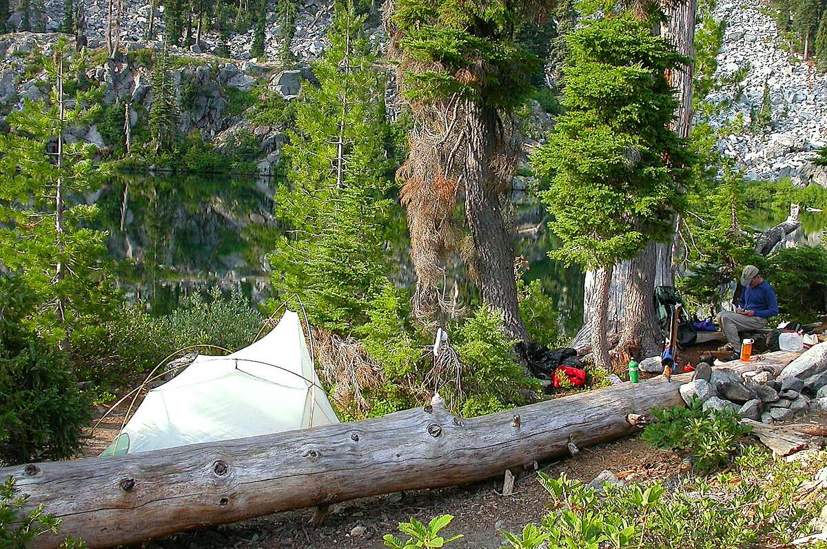 For a solitary camping trip during the coronavirus pandemic, Tom Steinstra recommends a trip to th Marble Mountain Wilderness. In this image, Michael Furniss writes in his trail note diary at a trail camp at Monument Lake in Marble Mountain Wilderness,