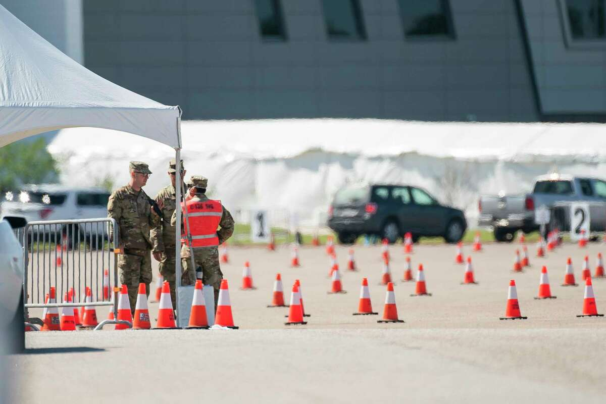 Members of the National Guard direct traffic at the city's COVID-19 testing site at Delmar Stadium in Houston, Wednesday, April 1, 2020. People who come to the site must have been pre-screened and must bring a unique identification number to access the testing site.