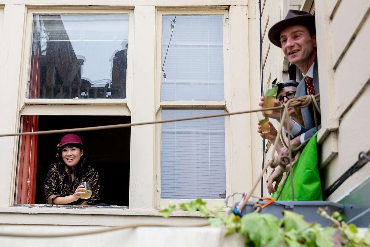 (From left) Judy Tsang, Sarah Kingston and Tom Broxton sip cocktails and chat from their apartment windows while their neighbors pass around a bucket of cocktail ingredients, snacks and other communal goods from window to window of their adjacent apartment buildings in San Francisco, Calif. Saturday, June 20, 2020. Since the shelter-in-place order was implemented, these neighbors began holding a weekly happy hour named Bucket Bar from the windows of their homes to promote social distancing while still being social.