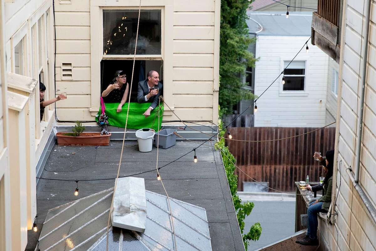 (From left) Judy Tsang, Sarah Hingston, Tom Broxton and Alexis Bustos raise their glasses and cheer after receiving the cocktails through a bucket filled with ingredients, snacks and other communal goods from window to window of their adjacent apartment buildings in San Francisco, Calif. Saturday, June 20, 2020. Since the shelter-in-place order was implemented, these neighbors began holding a weekly happy hour named Bucket Bar from the windows of their homes to promote social distancing while still being social.