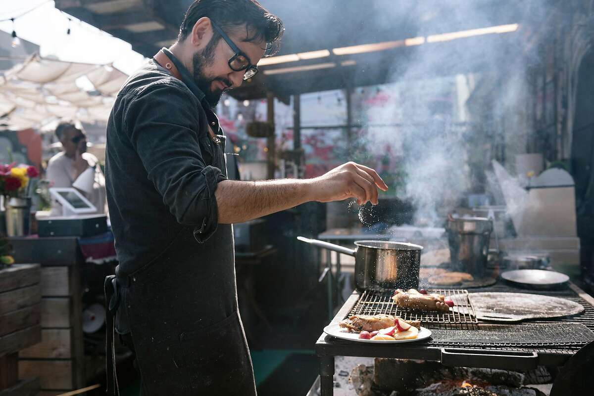 Chef and owner Anthony Salguero sprinkles salt onto chicken cooking on the wood-fired grill at Popoca, at the Classic Cars West beer-garden in Oakland, California, on Saturday, March 22, 2020.