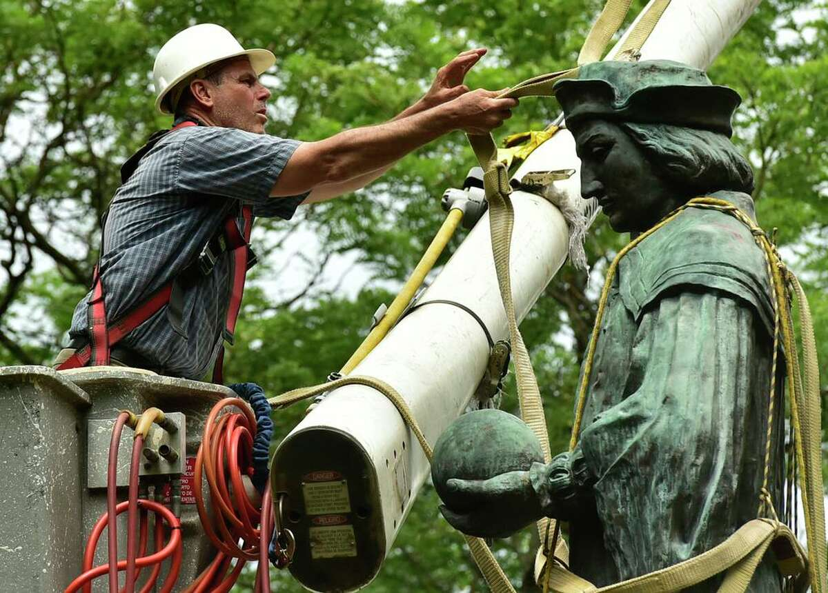 The statue of Christopher Columbus is removed from Wooster Square Park, in New Haven, Conn. Wednesday, June 24, 2020.