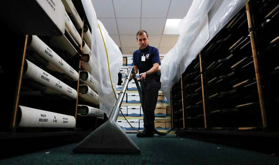 Jaime Fernandez helps dry out carpet of the Montgomery County's record management room after the roof drain of the county courthouse's annex atrium broke during Thursday's thunderstorms. The water flooded portions of four floors of the building, including three courtrooms and part of the county's record management room. Photo: Jason Fochtman, Houston Chronicle / Staff Photographer / 2020 © Houston Chronicle