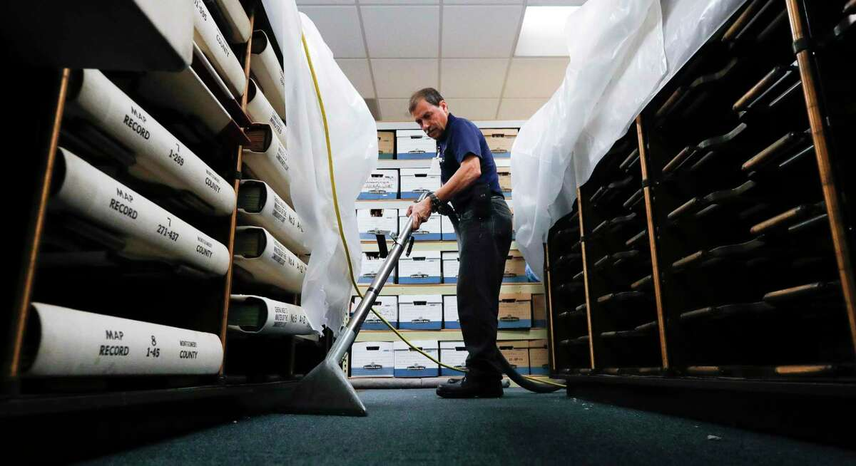 Jaime Fernandez helps dry out carpet of the Montgomery County's record management room after the roof drain of the county courthouse's annex atrium broke during Thursday's thunderstorms. The water flooded portions of four floors of the building, including three courtrooms and part of the county's record management room.