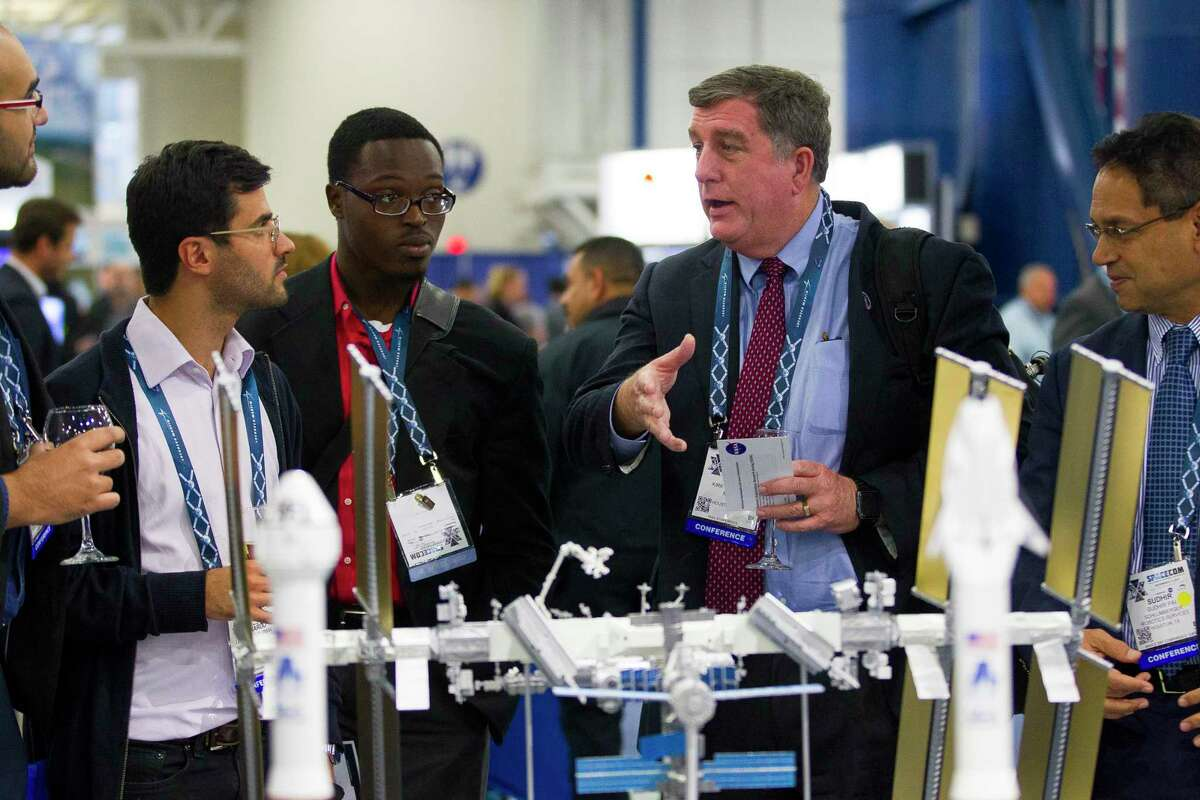 Kirk Shireman (center), who manages NASA's International Space Station program, talks to visitors to NASA's exhibit at SpaceCom during an opening reception at the George R. Brown Convention Center, Tuesday, Dec. 5, 2017, in Houston. ( Mark Mulligan / Houston Chronicle )
