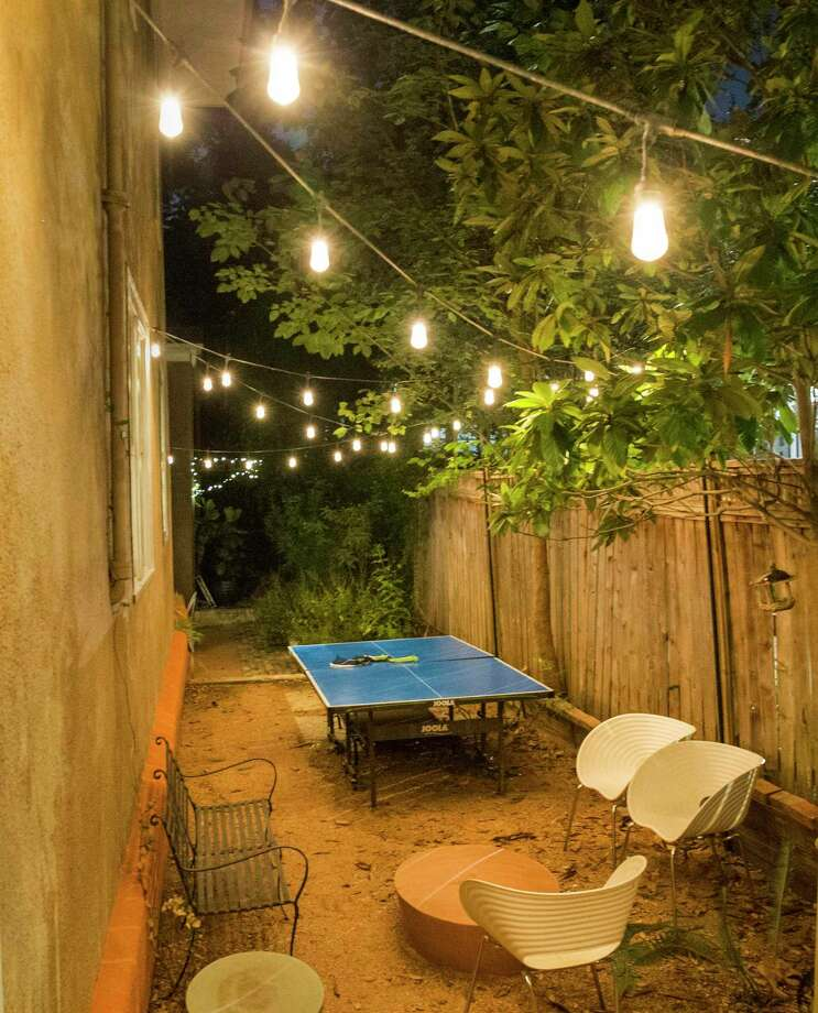 "Furniture and a table tennis table are lit by lights hanging from a wire zigzagging above a patio area on the side of Bill Fisher's house on the block of 2800 N. Main in San Antonio on Monday, Aug. 26, 2019. According to the Martha Stewart website, ""Lighting is one of the easiest (and least-expensive) ways to cast an enchanting spell on any outdoor space."" Photo: Daniel Carde / Special Contributor / Daniel Carde"