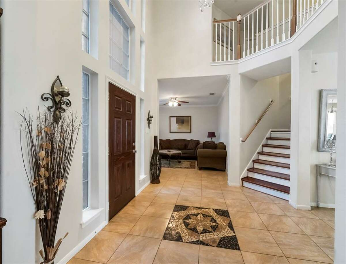 Its foyer welcomes guests into a two-story grand room.