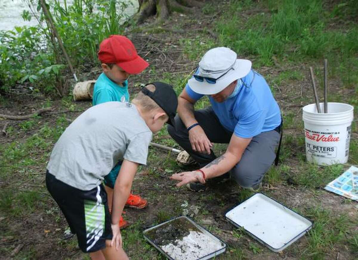 Kids sift through pond silt at The Nature Institute to learn more about the area.